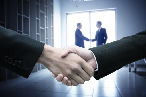 商談後に握手を交わす外国人男性