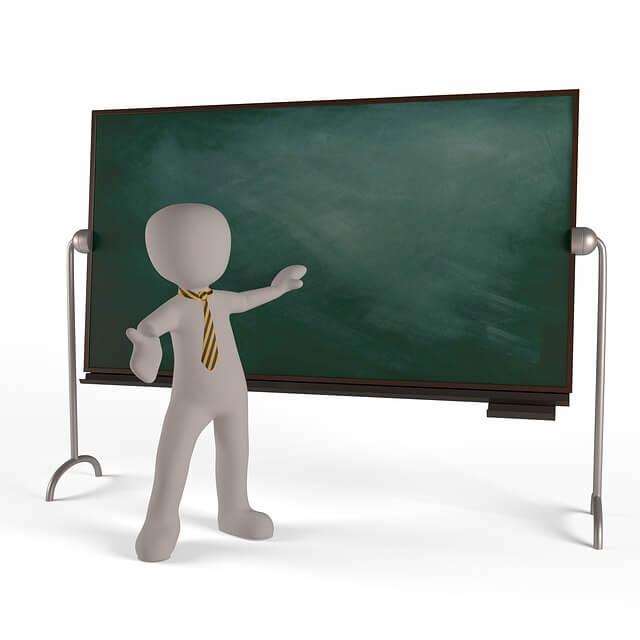 黒板を使って生徒たちを集団指導する英会話スクールの講師