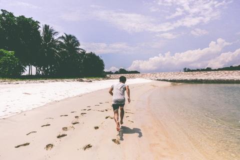 海岸を裸足で走る男性