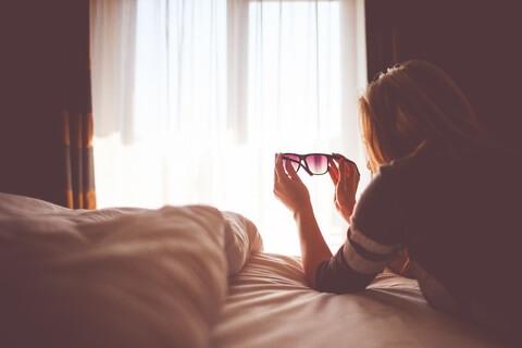 部屋のベッドにたたずむ女性