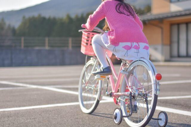 補助輪をつけて自転車をこぐ子供