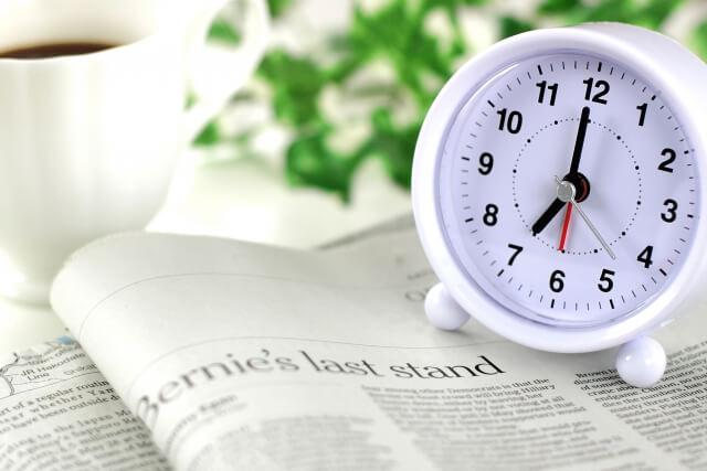 朝7時を指す目覚まし時計と英字新聞