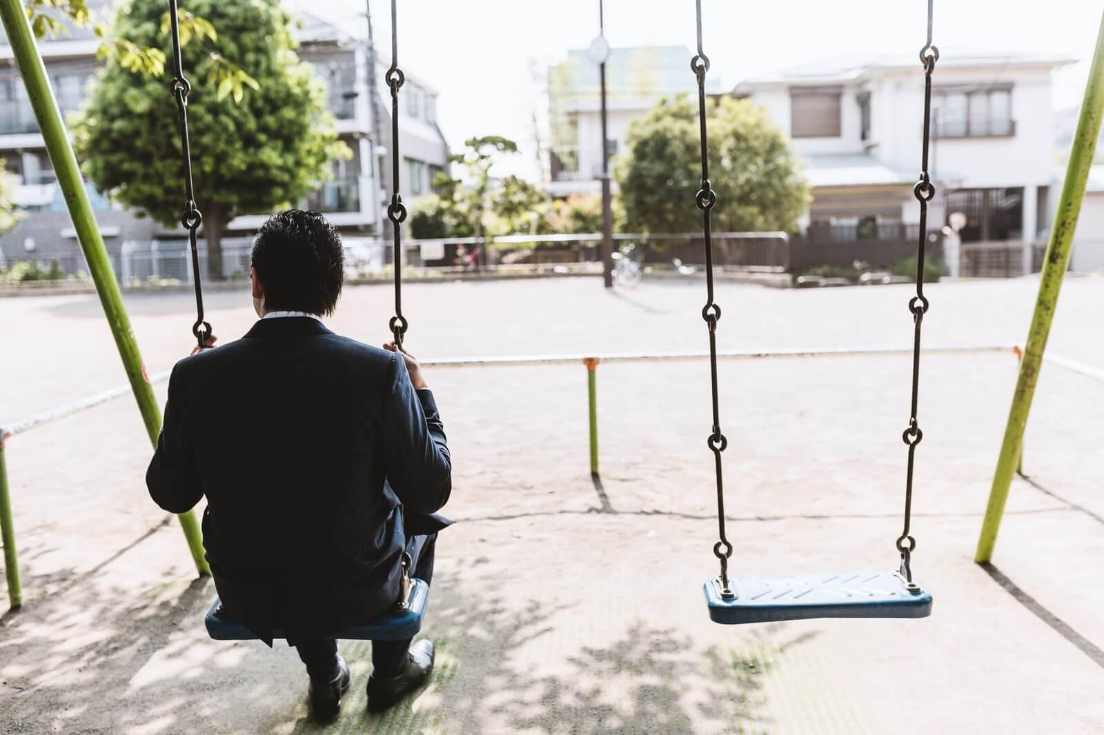 落ち込んで公園のブランコに座っているサラリーマン