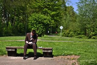 公園のベンチで寝る会社員